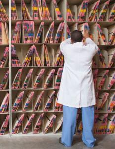 médico de espaldas en repisa con documentos